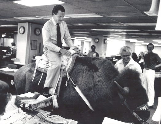 City editor Bill Cox rides a buffalo through the newsroom, 1983