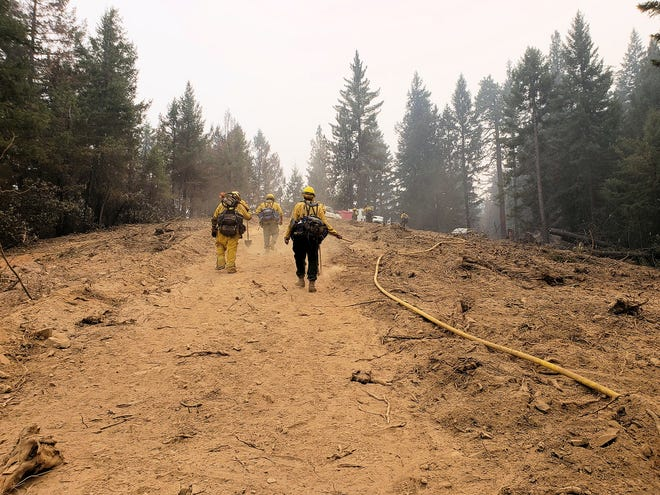 Texan firefighters walk up a mound of dirt outside of Redding, California. They had been deployed to the Golden State for two weeks in August to help fight the devastating Carr Fire.