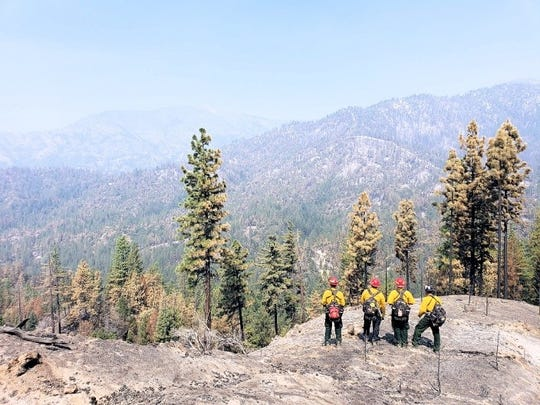A group of Texan firefighters look over a mountain outside of Redding, California.