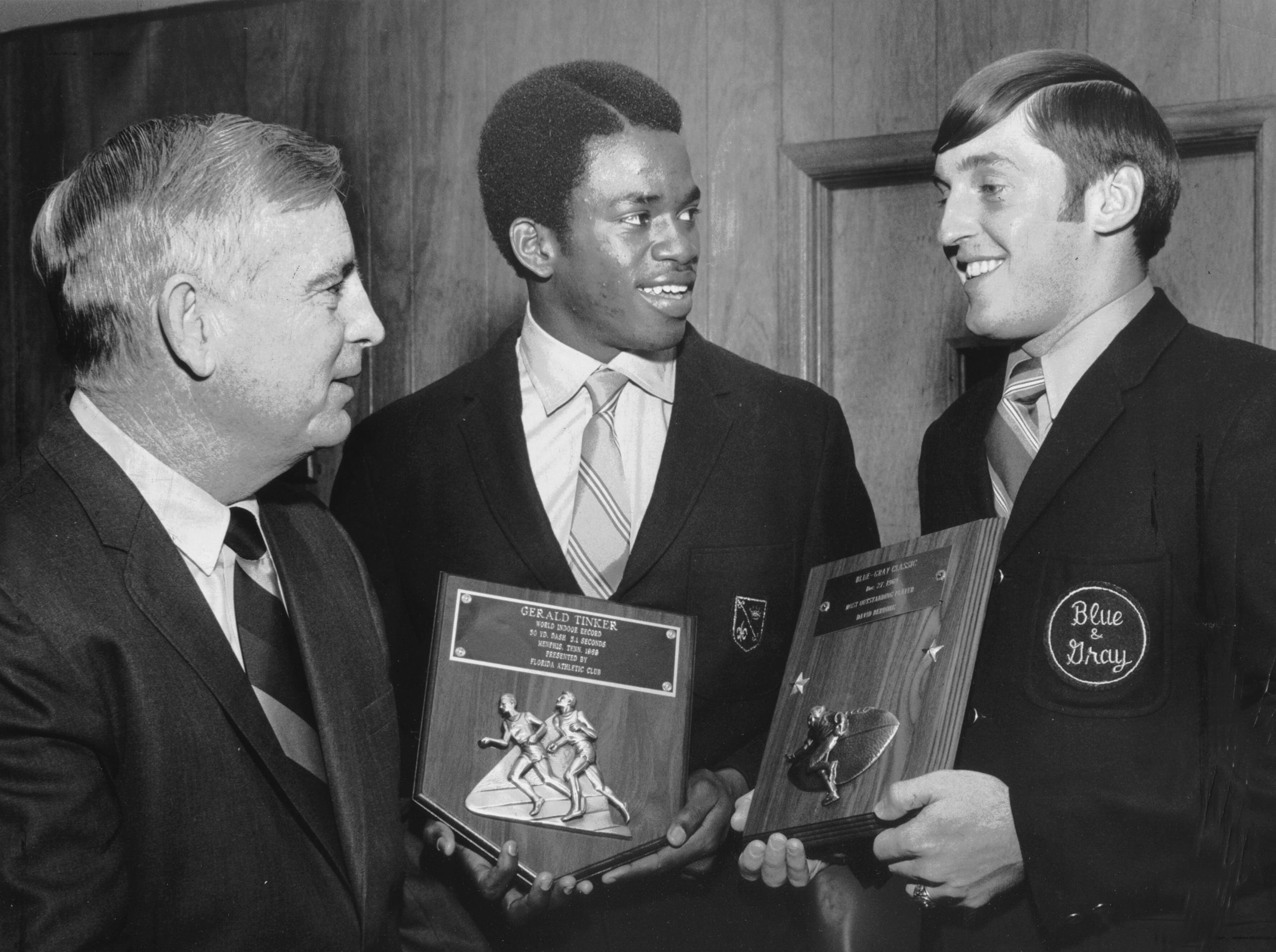 Memphis State?s Billy Murphy (left), Gerald Tinker (center) and David Berrong discuss hardware the two Memphis State University athletes had collected in December 1969. Tinker holds a plaque proclaiming his world indoor record in the 50-yard dash at 5.1 seconds, presented by the Florida Athletic Club, while Berrong holds a plaque for being the most outstanding player in the Blue-Gray Classic football game on Dec. 27, 1969.