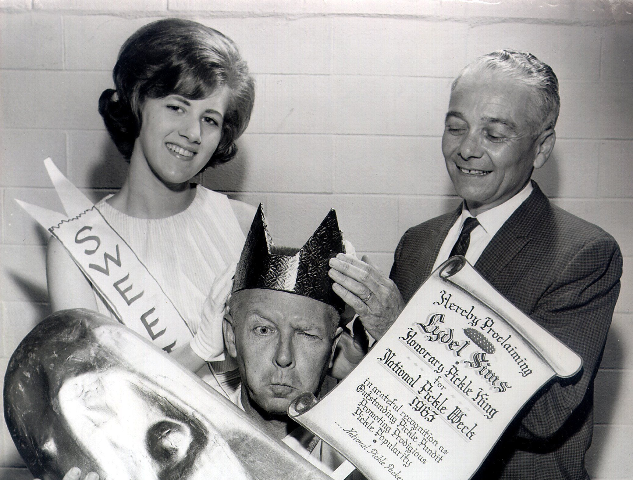 Columnist Lydel Sims (center) of The Commercial Appeal is named Honorary Pickle King for National Pickle Week in 1963 by Berny Messinger (right). Benita Blackman looks on during the April 1963 coronation.