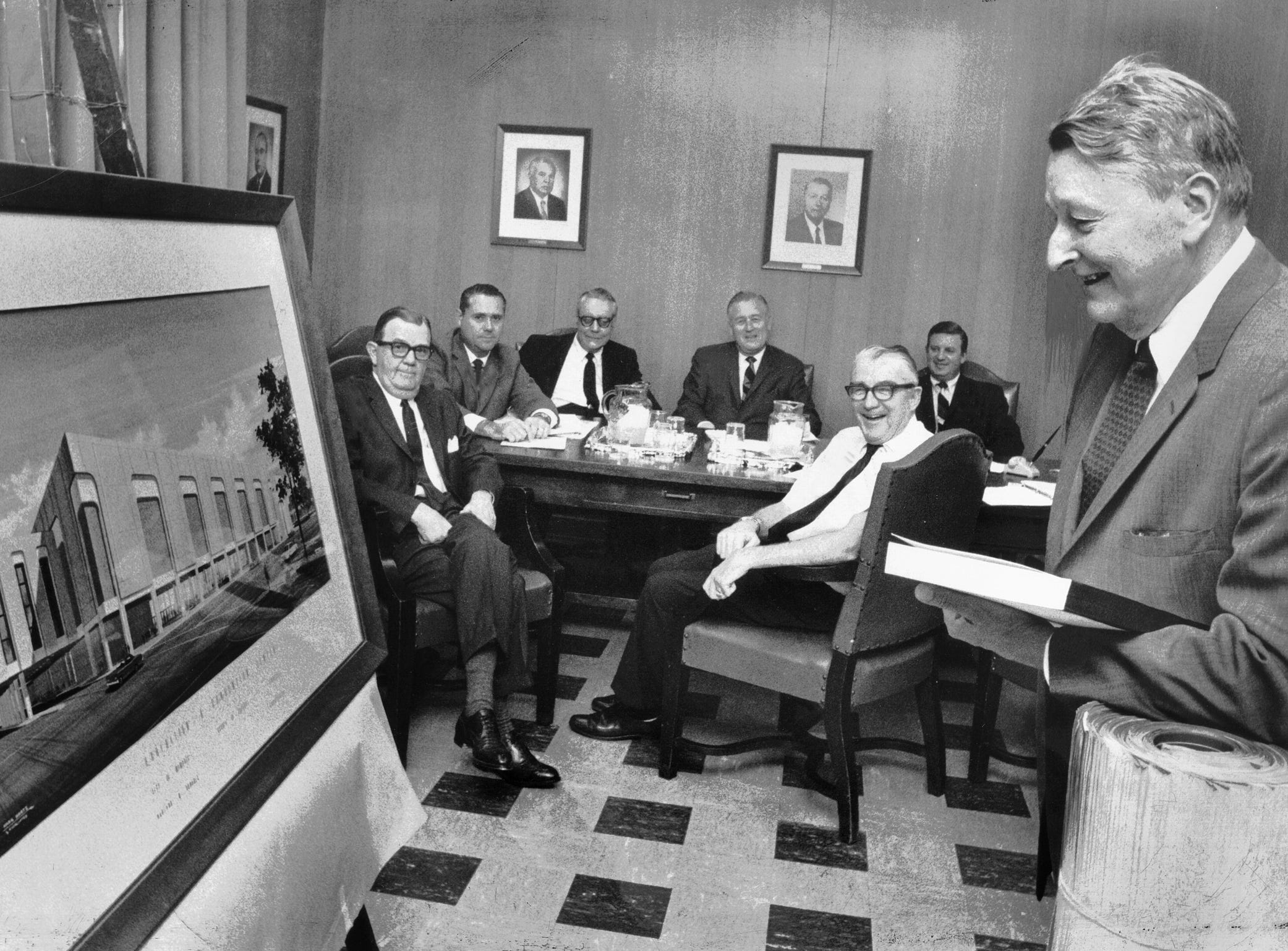 Leaning on 145 pages of blueprints and holding an inch-thick set of specifications, Everett R. Cook (right), Auditorium Commission chairman, looks at a rendering on Nov. 16, 1967, of the convention center that will later bear his name. Seated around the table (clockwise from left) are City Commissioner L.D. Ervin, Bill Van Hersh, Jim Woods, Lester Presson, architect Louis Haglund and auditorium manager Chauncey Barbour.