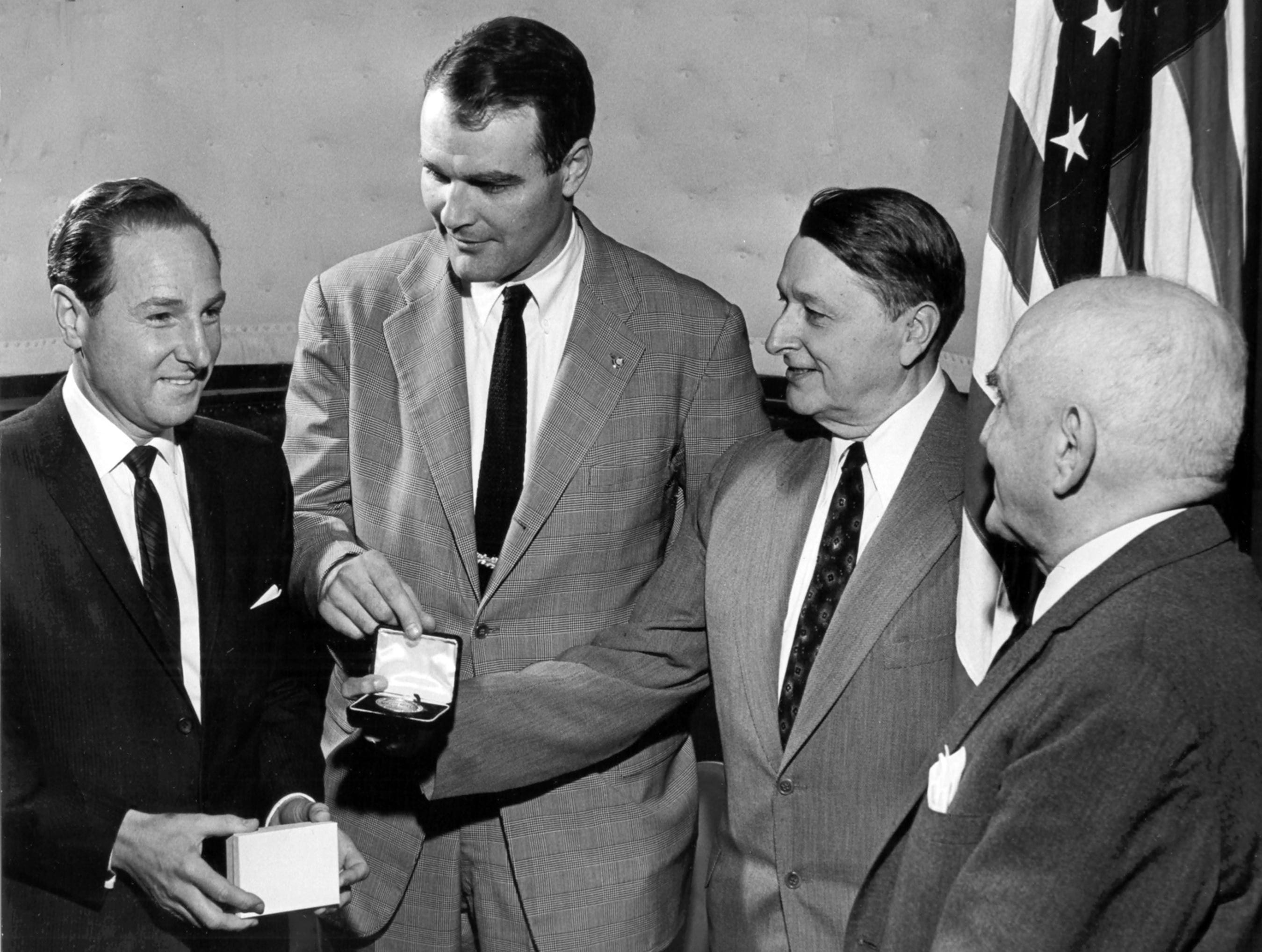 "Fred Goldsmith (left) received the kudos for his brother, Jack Goldsmith (not shown) on March 4, 1960, when the National Conference of Christians & Jews honored the latter at the Claridge Hotel. Admiring the medallion, which accompanied the citation, were (from left) Mayor Henry Loeb, Everett Cook and former mayor Walter Chandler. Mr. Goldsmith was snowbound in New York and unable to attend. The NCCJ citation described Jack Goldsmith as a ""merchant, philanthropist, soldier, president of Goldsmith's and (who) has supported the National Conference objectives, giving of his time and means."""