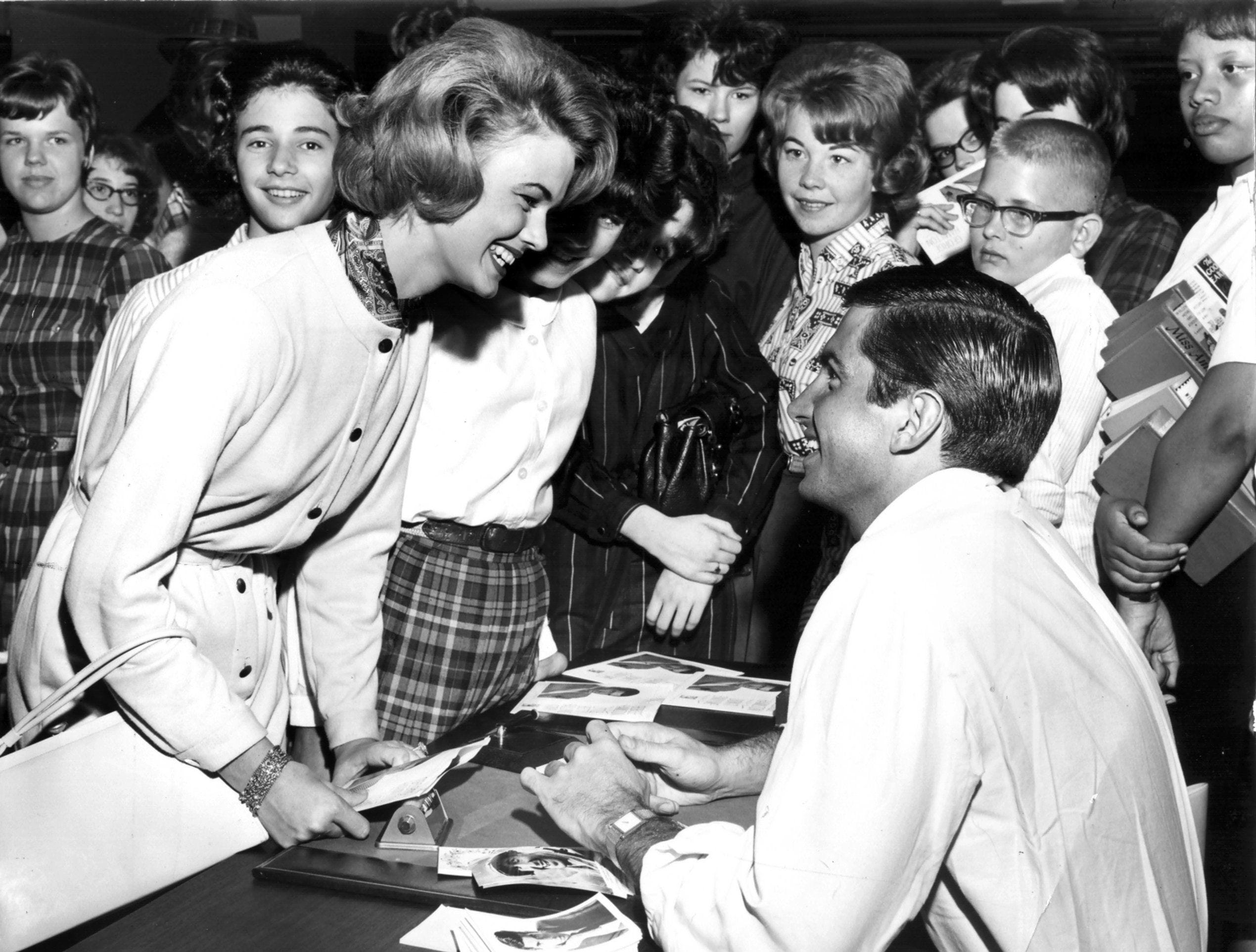 "Memphis-born movie-star George Hamilton was in Memphis on 19 Oct 1963 promoting his latest record, ""Don't Envy Me.""  Getting his autograph at Goldsmith's was Carey Dowdle, 17, daughter of Mr. and Mrs. B.C. Dowdle of 69 South Fernway."