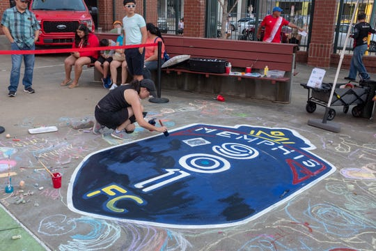 Yancy Willa-Calvo paints the Memphis 901 FC logo at Autozone Park.