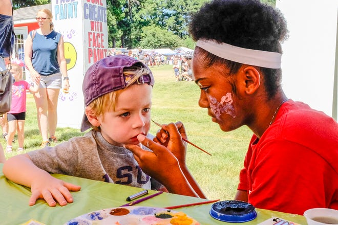 Carson Smith, 3, holds still as Alanna Lee paints Batman on his face at the 45th annual Germantown Festival in 2018.