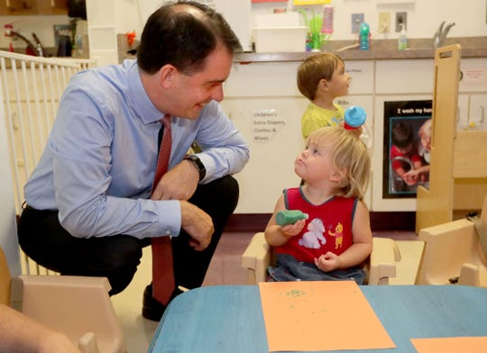 Gov. Scott Walker visits with 1-year-old Lacey Poeschl in the La Casa de Esperanza day care. Walker welcomed students on their first day of school at La Casa de Esperanza school in Waukesha on Tuesday.