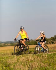 A mother and daughter cycle across the scenic Military Ridge State Park Trail.