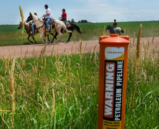 A group rides along the oil pipeline easement for Enbridge Inc. in Clark County south of Owen.