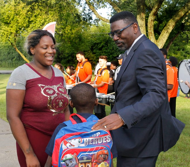 Ashanzti East (from left) and her son, Kameron Brown, 6, are greeted by MPS Superintendent Keith Posley.