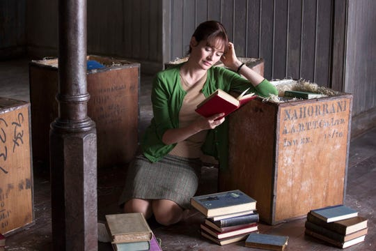 "Emily Mortimer unpacks books in her new store in ""The Bookshop."""