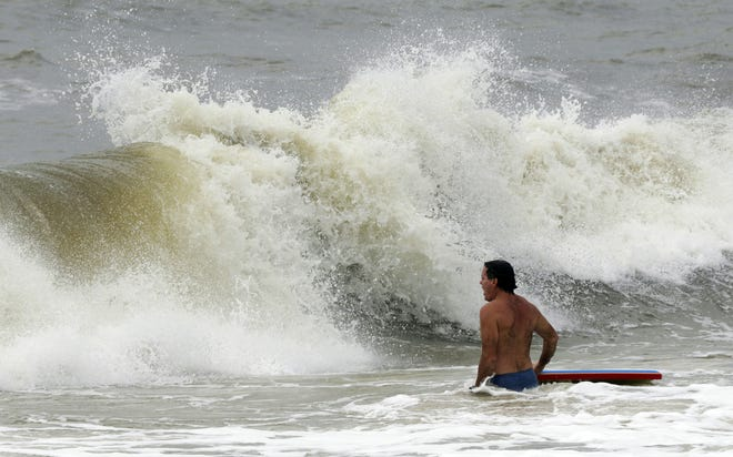 Chris Stebly tries to catch some waves as Tropical Storm Gordon heads towards the coast on Tuesday, Sept. 4, 2018, in Dauphin Island.