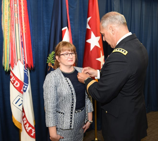 Gen. Gus Perna, commander of the Army Materiel Command, pins the Senior Executive Service pin to Renee Mosher's lapel during her Aug. 22 appointment ceremony at AMC headquarters, Redstone Arsenal, Alabama.