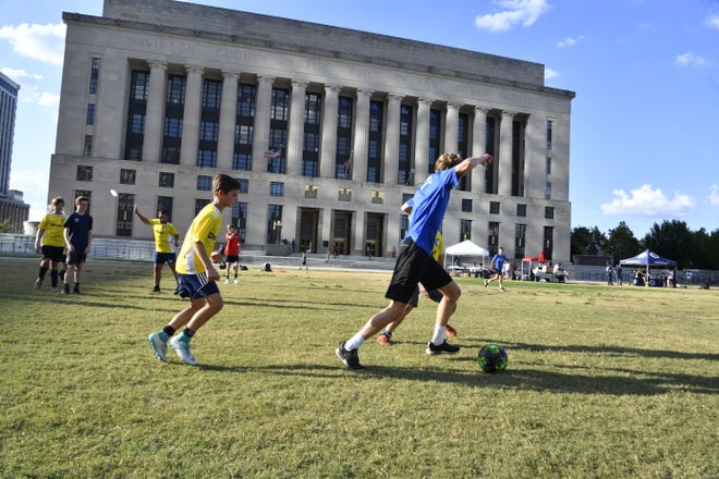 Kids kick a soccer ball around the lawn of Public Square Park in front of the Metro Nashville Courthouse on Sept. 4, 2018, ahead of the Metro Council's vote on a proposed Major League Soccer stadium at the city's fairgrounds.