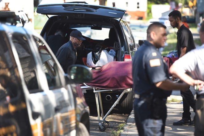 A body which was found in the Passaic River near the corner of North Straight and Lafayette Streets, is carried out on a stretcher and placed in a van in Paterson on 09/04/18.