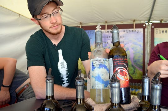 Jacob Anderson, 28, assistant winemaker for Sheehan Winery, displayed their most popular red and white wines; White Cielo Dulce and Red Danza del Fuego.