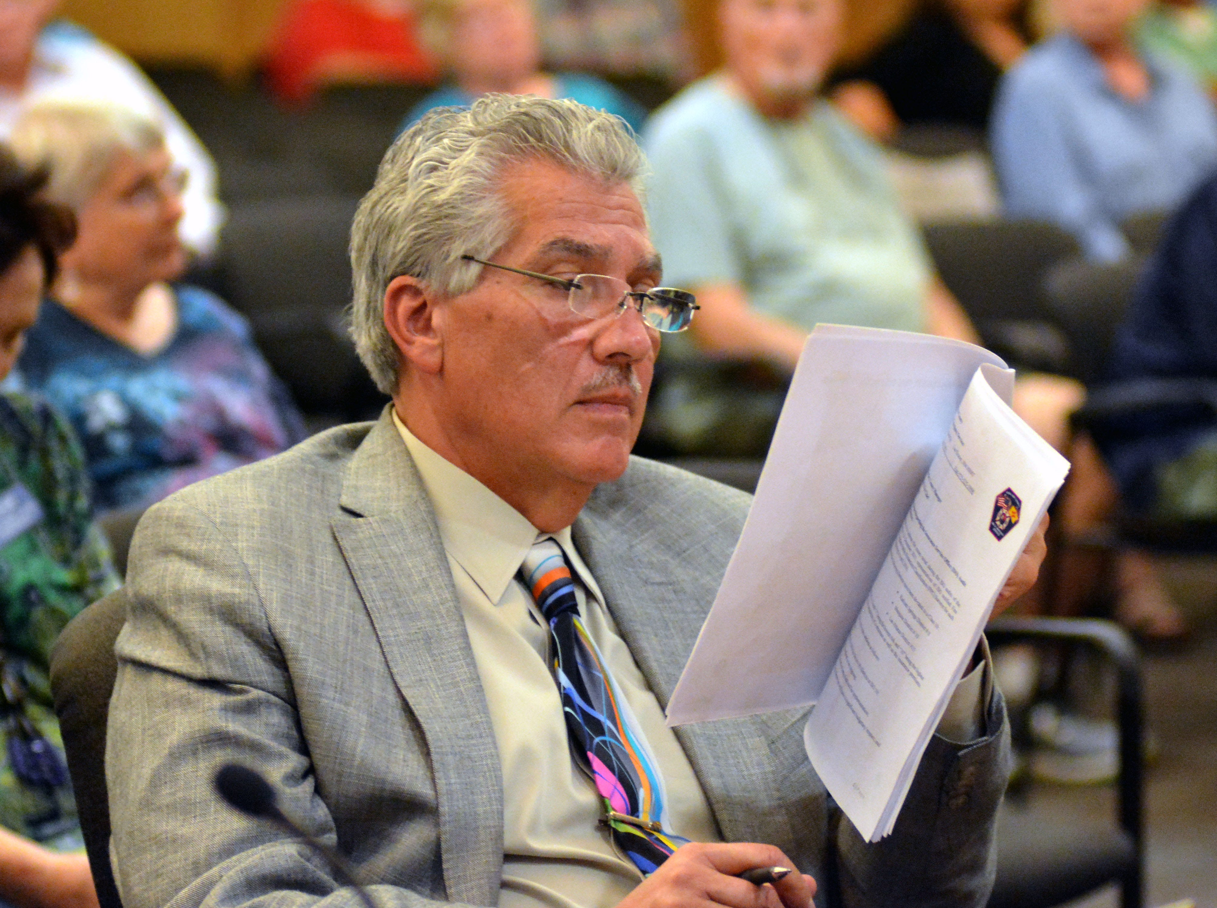 Doña Ana County Manager Fernando Macias looks over a resolution as residents voice their opinions Tuesday, Sept. 4, 2018, at a special meeting of the Doña Ana County Commission.