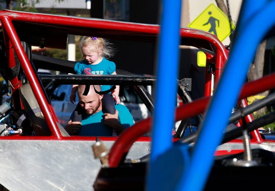 Jacob Bean and his daughter, Aliyah Bean, 2, take in the Fall Crawl on Friday Sept. 9, 2016, on Main Street. The car show preceeds the World Extreme Rock Grand National Championship, which takes place Saturday and Sunday at Chokecherry Canyon.