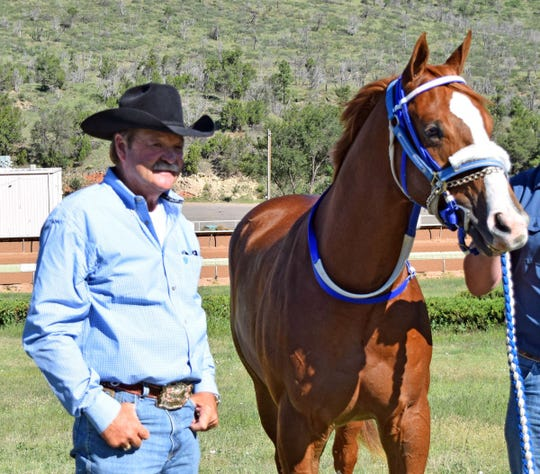 Trainer Blane Wood stands next to All American Futurity winner Apocalyptical Jess at Ruidoso Downs Race Track.