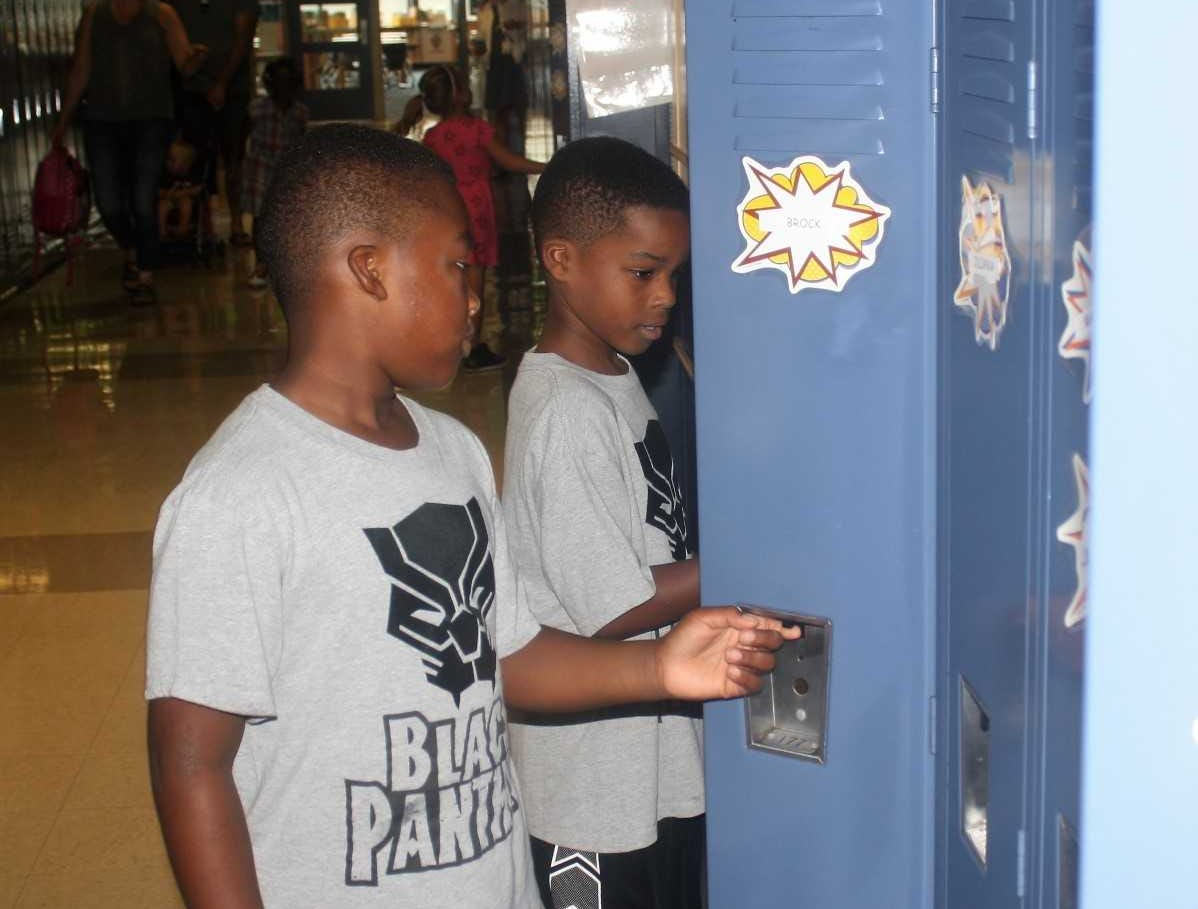 Twins Ashton and Brock Blackwell, both second-graders at Sayre Elementary School in South Lyon, finish organizing their lockers.