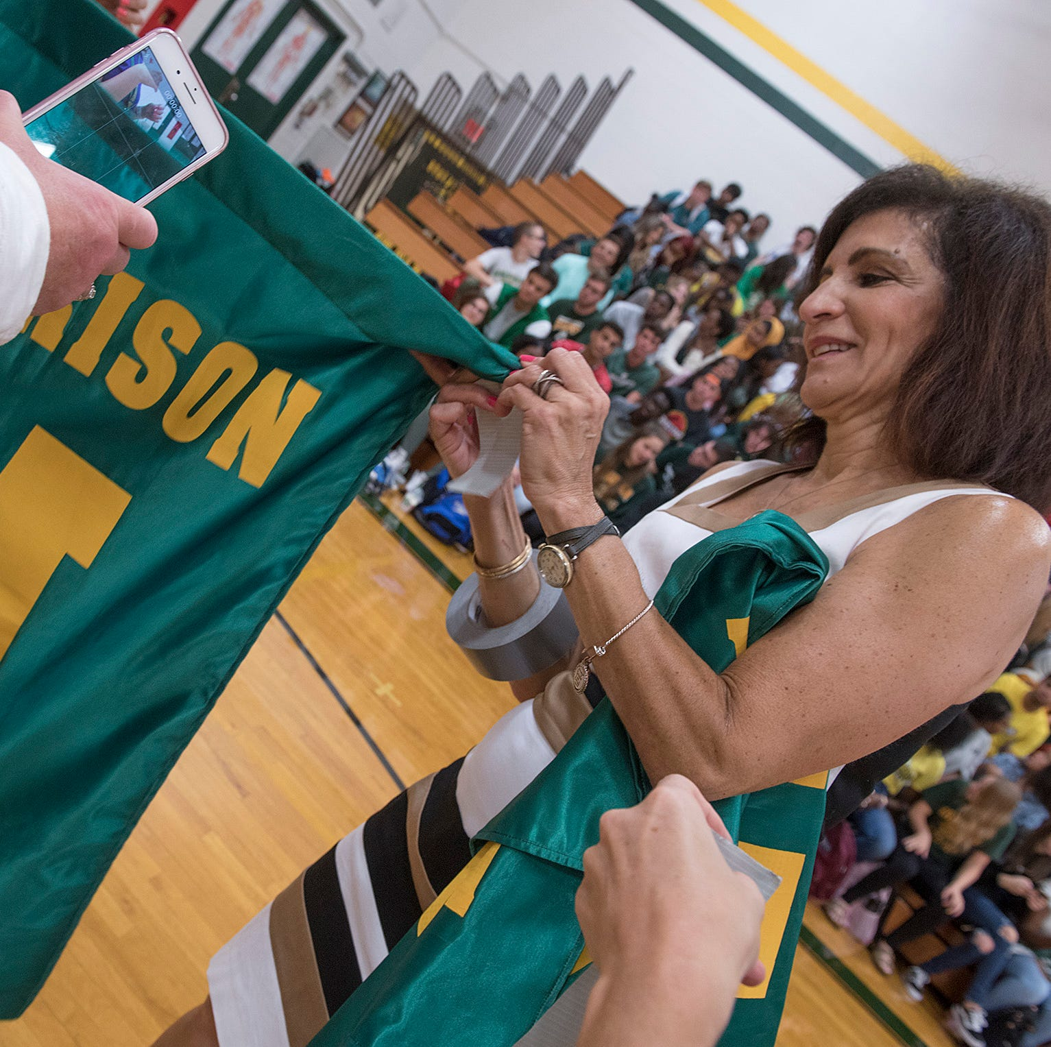 Assistant Principal Angela Leach applies tape to school banners for a portrait of the senior class.