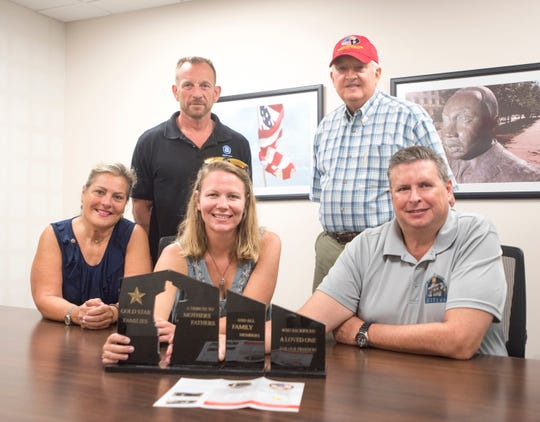 Clockwise from back left, retired U.S. Marine Corps Lt. Col. Dave Glassman, Jack Brown, Ed Spears, Ashley Lukasiewicz and Suzi Fernandez pose with a model of a Gold Star families memorial they are working to bring to Pensacola.