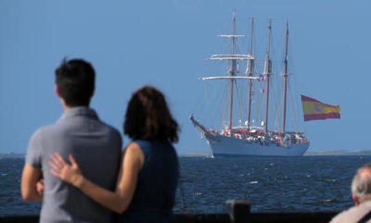 Onlookers watch the Royal Spanish Navy tall ship Juan Sebastian de Elcano sail into Pensacola Bay.