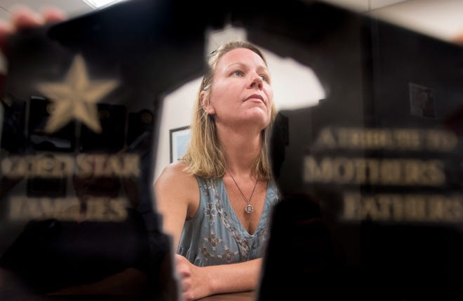 Ashley Lukasiewicz is framed by a model of the Gold Star Families memorial that she and a group are working to create in Pensacola.