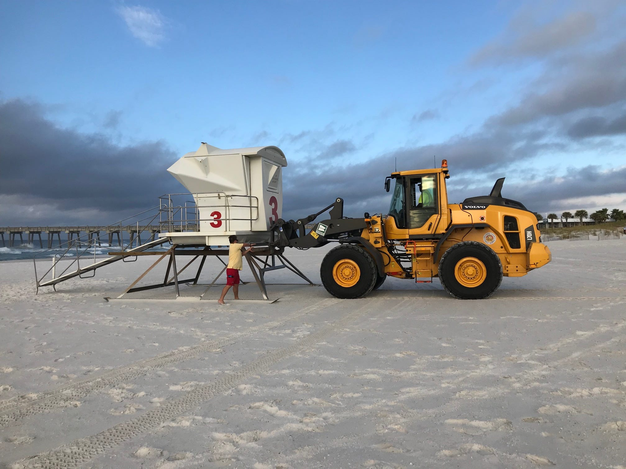 Lifeguards pull towers back to the dune line in advance of Tropical Storm Gordon early Tuesday morning.