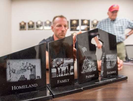 Jack Brown, right, looks on as retired U.S. Marine Corps Lt. Col. Dave Glassman displays a model of the Gold Star Families memorial that he and a group are working to create in Pensacola.
