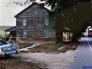 In this police file photo, crime scene tape surrounds the Oxford Township home of Edna Laughman, who was raped and murdered on August 13, 1987.