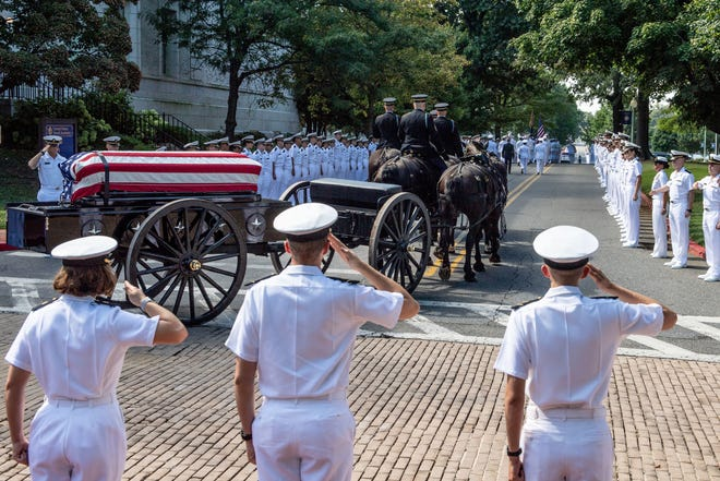 Midshipmen salute the casket of Sen. John McCain as a horse-drawn caisson transports his flag-draped casket to the United States Naval Academy Cemetery for his burial service, Sept. 2, 2018.