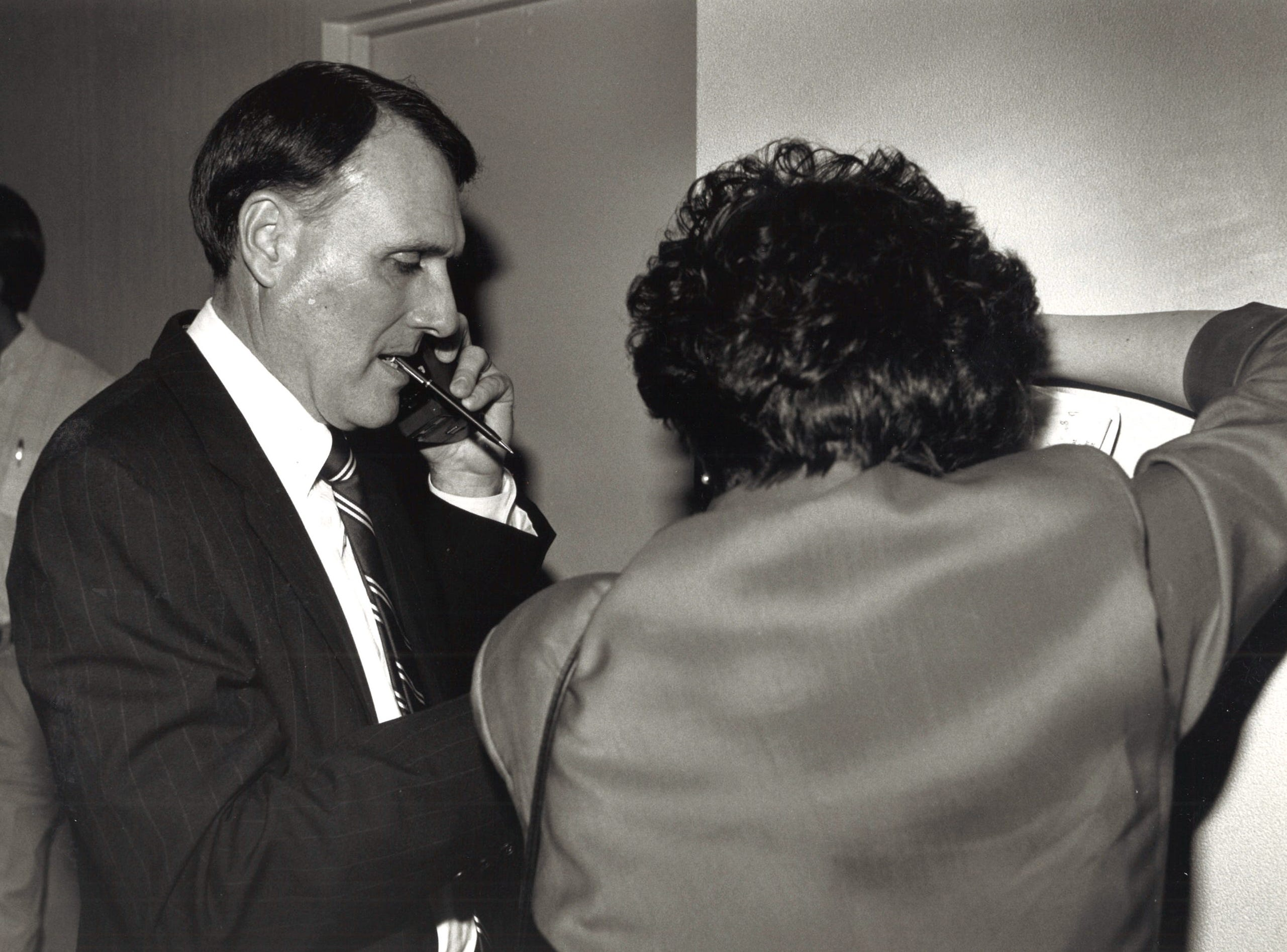 Jon Kyl holds his pen in his teeth while talking on a mobile phone. He was calling to get election results from other states, Nov. 7, 1990.