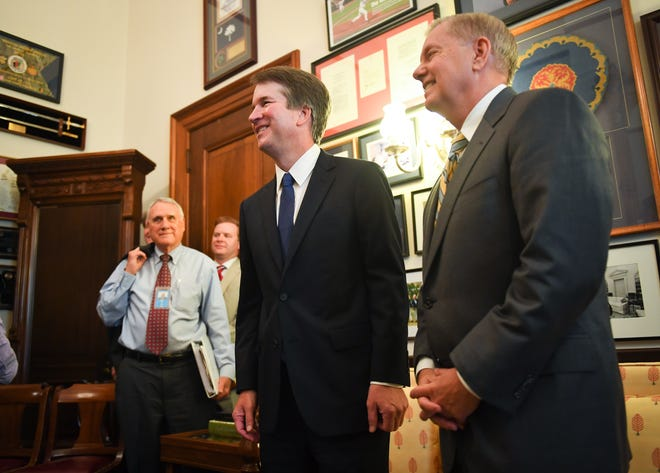 Supreme Court nominee Brett Kavanaugh and Senator Lindsey Graham (R-SC), right, pose for the media in Graham's Russell Senate office before meeting on Capitol Hill. Former Senator Jon Kyl (R-AZ), left, was escorting the nominee around Capitol Hill.