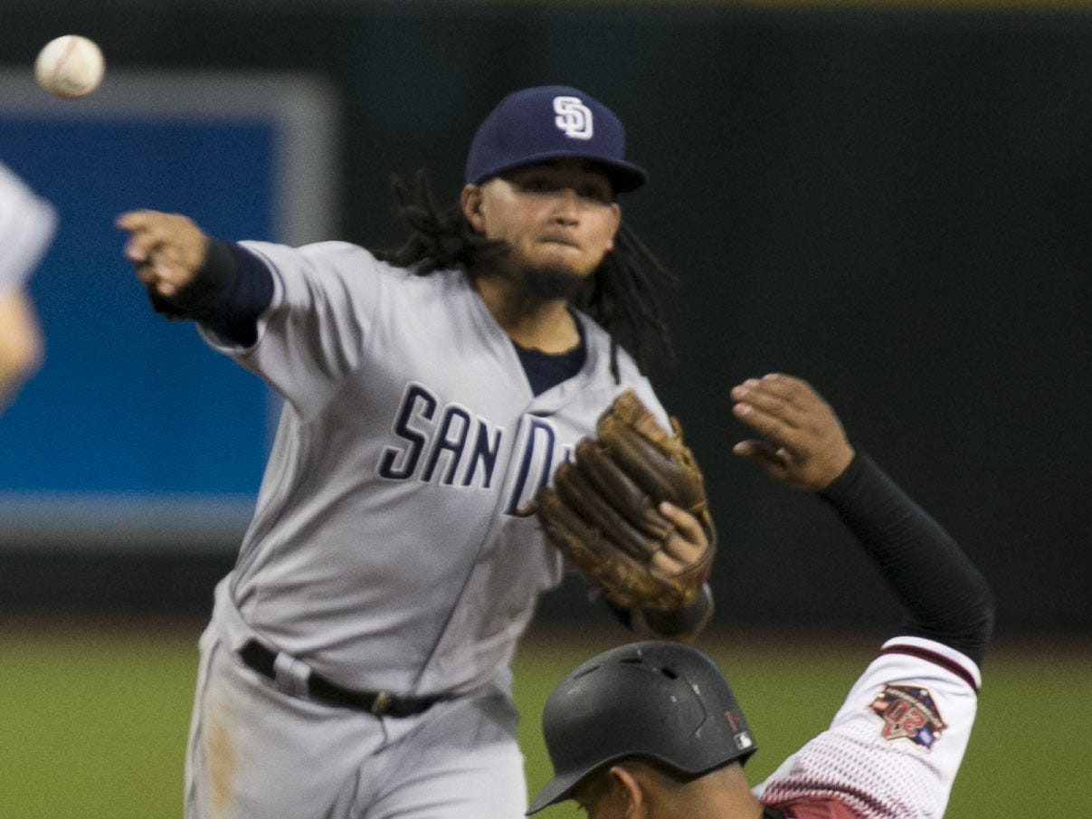 Padres shortstop Freddy Galvis turns a double play against the Diamondbacks Eduardo Escobar during the sixth inning of the major league baseball game at Chase Field in Phoenix on Monday, September 3, 2018.