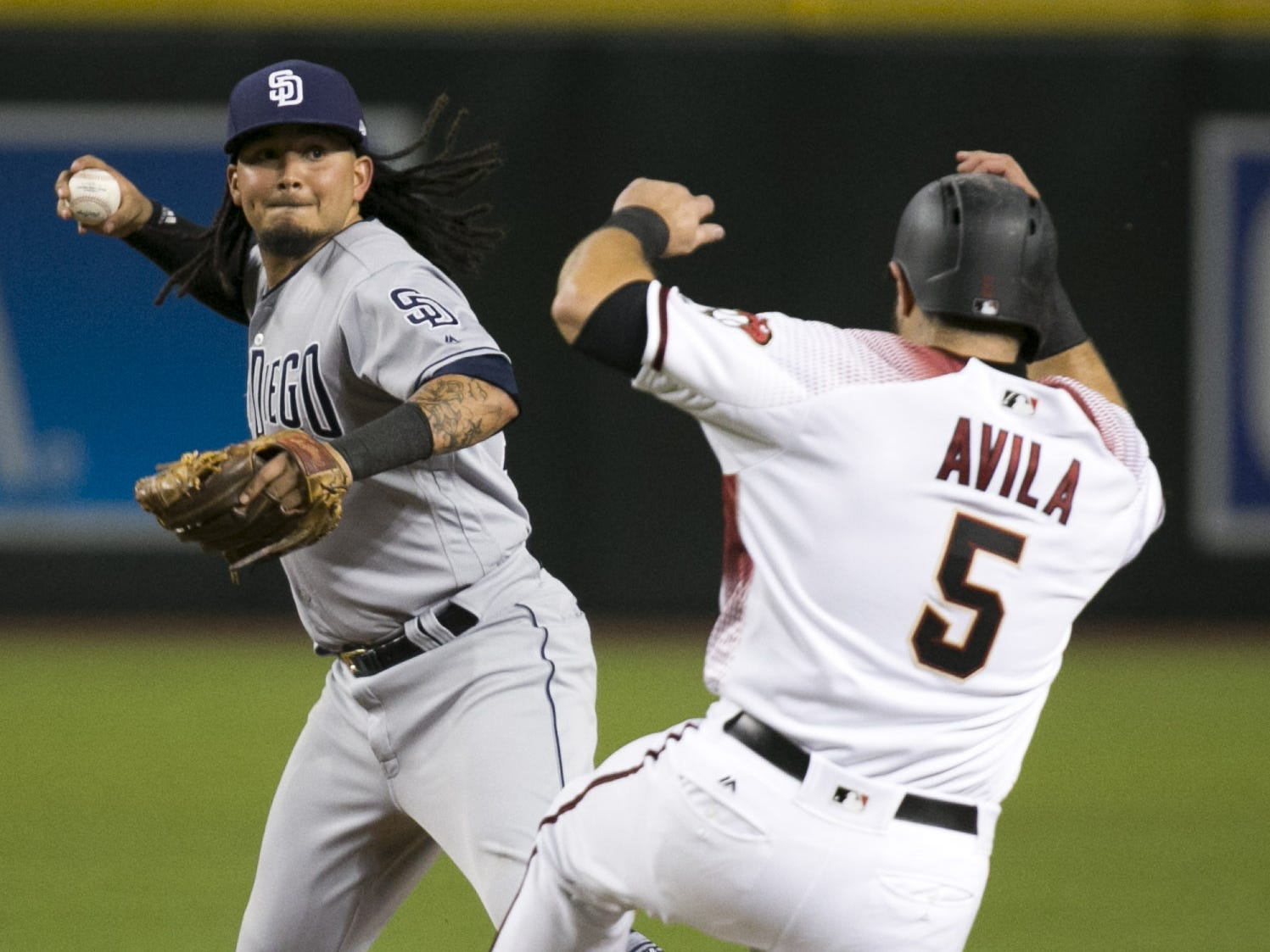 Padres shortstop Freddy Galvis turns a double play against the Diamondbacks Alex Avila during the fifth inning of the major league baseball game at Chase Field in Phoenix on Monday, September 3, 2018.
