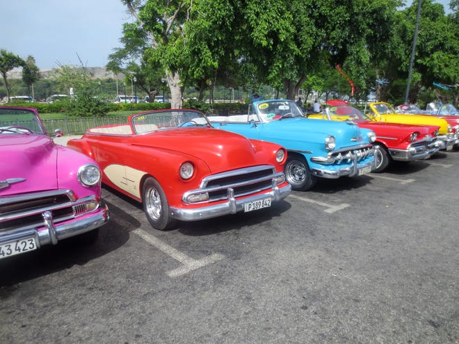 Vintage American convertibles from the 1950s parked in downtown Havana.