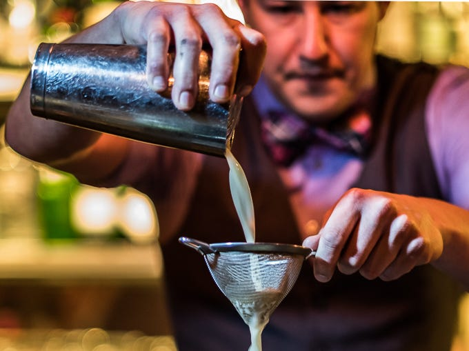 A bartender pours a cocktail at Crust Pizzeria and Italian Restaurant.