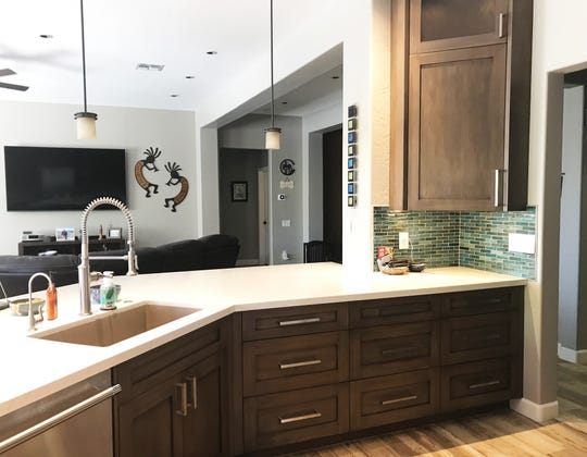 The homeowners needed more storage and they achieved this by eliminating the soffit and having the cabinetry go to the ceiling. They also installed cabinets on the outside of the kitchen island (pictured here). These have no hardware and open by magnetic latch so you can't tell there is storage in there.
