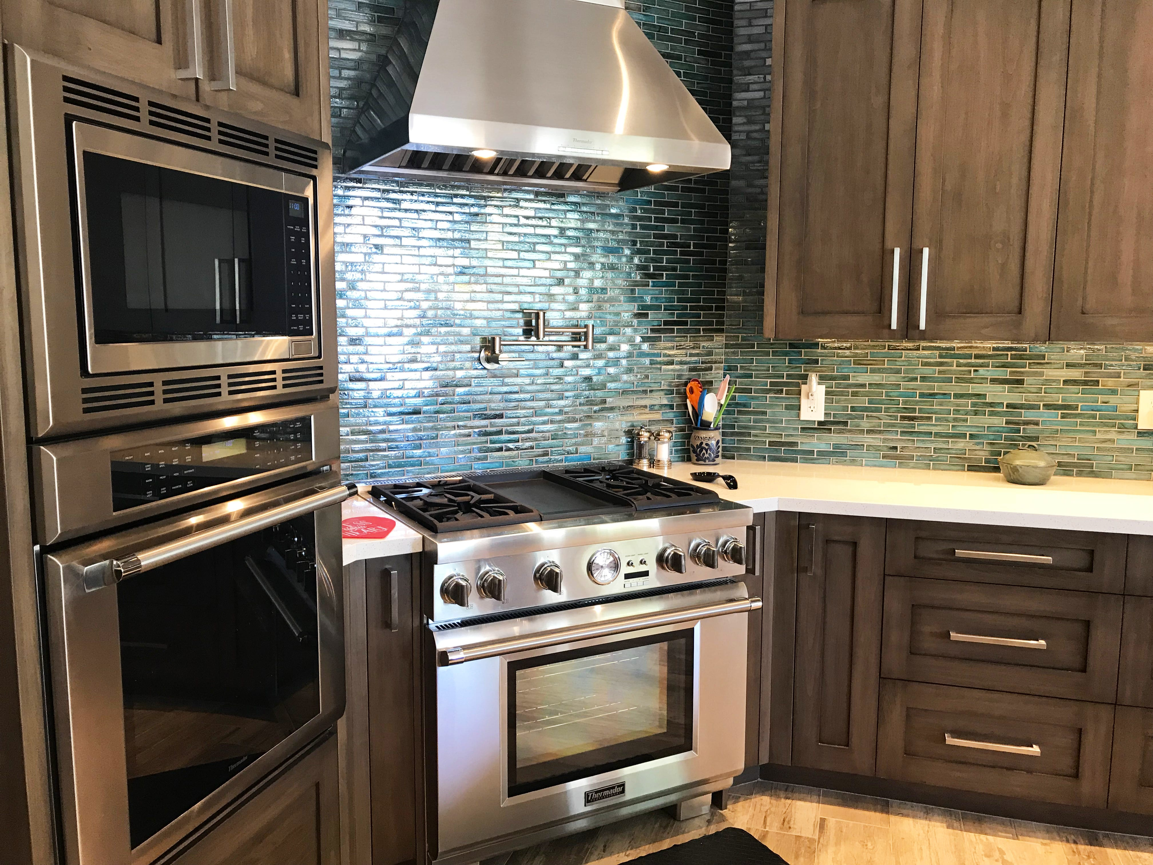Custom made stained alder wood cabinets and iridescent blue backsplash tiles cost $29,000 and $2,000 respectively. Dave McNay installed the tiles himself.