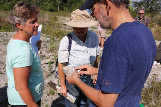 Bruce Simonson, retired professor of geology at Oberlin College, points out the prevalence of coral fossils in the limestone at the Curilla Preserve on Kelleys Island.