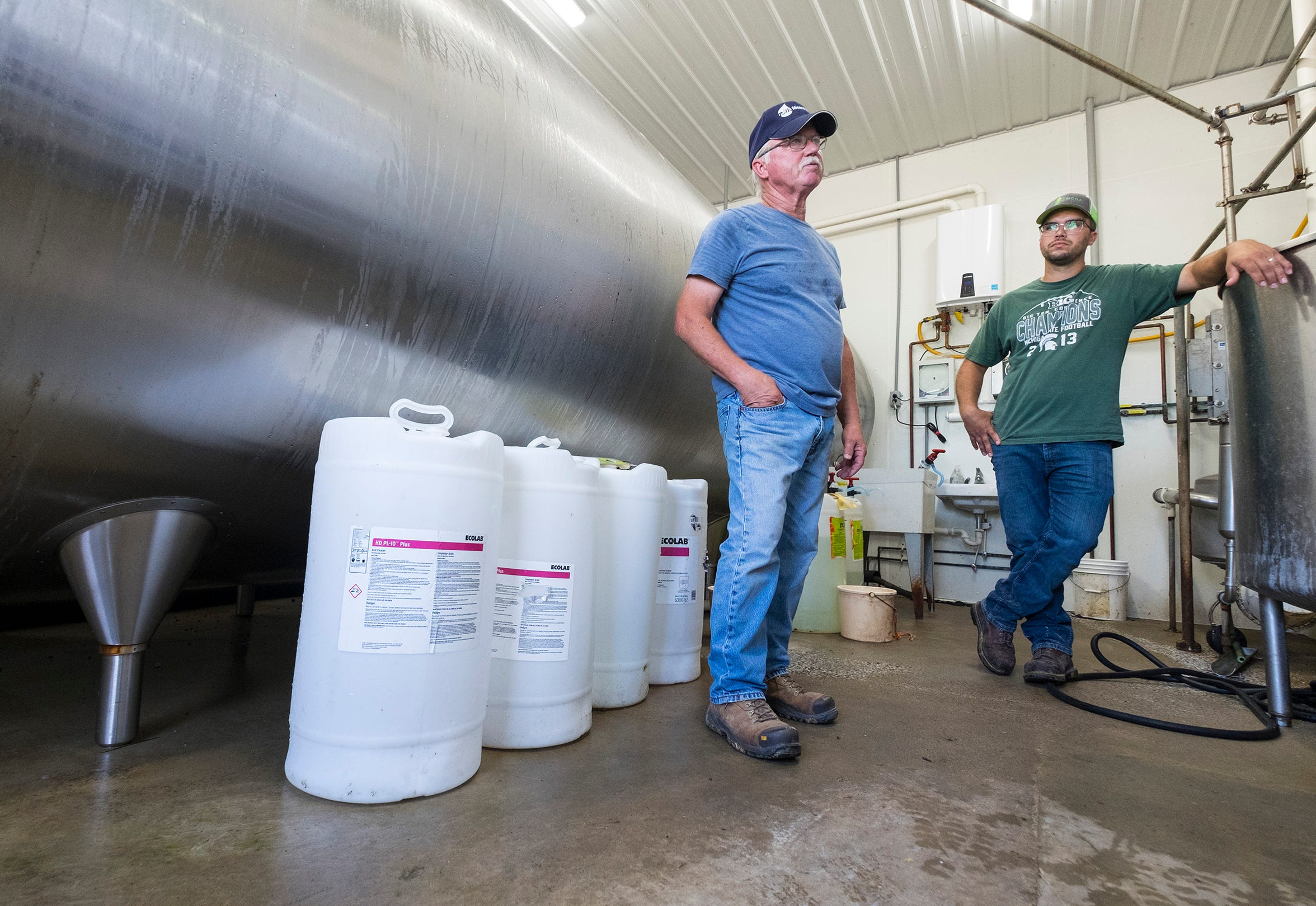 Jim Reid, left, and his son Jeff talk next to a milk cooler Tuesday, Sept. 4, 2018. Dairy farmers are increasingly facing difficulties to stay in business amid too much product for too little demand, falling prices and Donald Trump's trade negotiations.