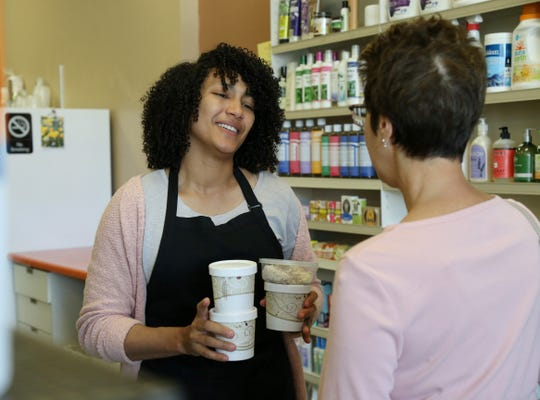 Inga St. Juste brings Andrea Ostwald's order to her at Eden Life Market in Pleasant Valley on August 23, 2018.