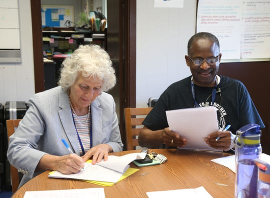 From left, Poughkeepsie City Schools interim superintendent Kathleen Farrell and acting principal Ronald Jackson sign off on paperwork for August graduates at Poughkeepsie High School, on August 28, 2018.