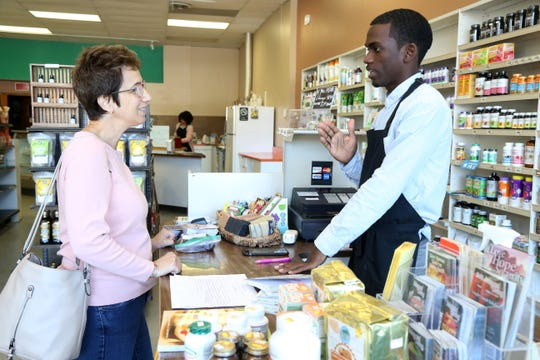 Andrea Ostwald of Pleasant Valley purchases goods from Renoir St. Juste at Eden Life Market in Pleasant Valley on August 23, 2018.