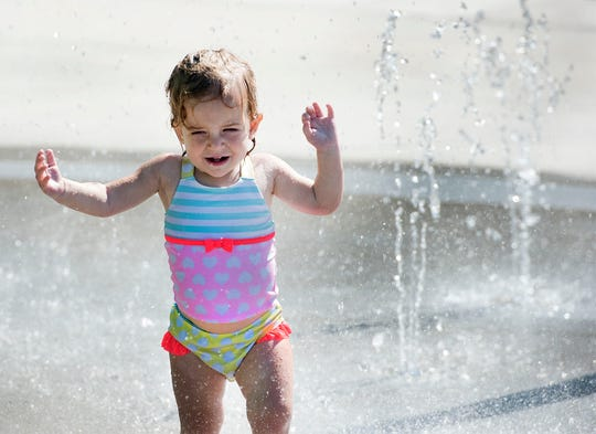 Two-year-old Deila Bobb cools off at the splash pad at Chambersburg Aquatic Center on Tuesday, September 4, 2018. The rest of the pool is closed, but toddlers are able to cool off inside the gated area.