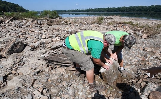 Hellam Township worker Curt Ferree, left, and resident Glenn Musser grab the base for a Civil War marker Tuesday that was found after it was washed out into the Susquehanna River from along River Road in Hellam Township during Friday's flash floods. The new  land mass the men are standing on was created by the storm erosion and extends out into the river. Ferree was working to reopen the road that crosses Dugan's Run on River Road when he went to help Musser lift the stone.