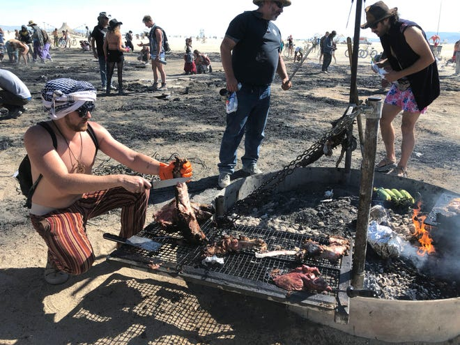 Ricardo Calmon slices up pork for burners on Sunday morning, Sept. 2, 2018. The meat was cooked on the embers of the burned Man effigy.