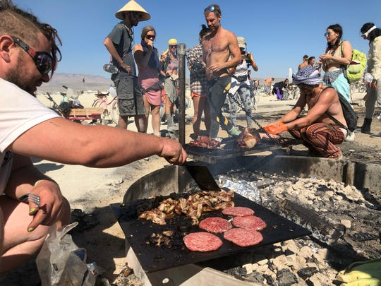 Brandon Emerson and Ricardo Calmon cut up pork and grill burgers and bacon for burners on Sunday morning, Sept. 2, 2018. He started helping the group HAMM, which butchers and cooks whole animals at Burning Man and other events to give people a better understanding of where their meat comes from.