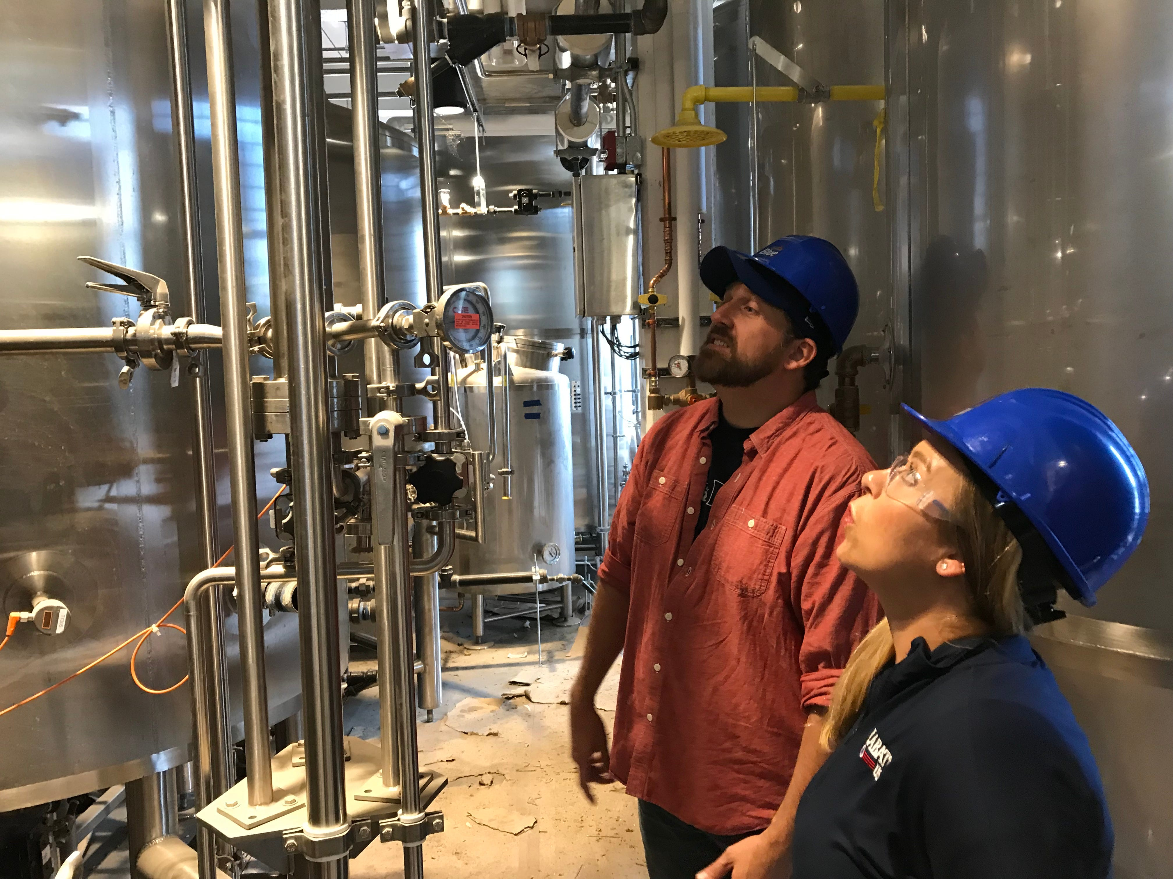 Brewer Ryan Brady and Brinn Johnson, director of retail strategy and brand development for Labatt USA, inspect the new brewing equipment at the Labatt Brew House in Buffalo.
